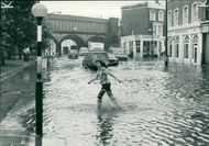 Floods 1966-1989:A london woman making heavy weather of crossing.