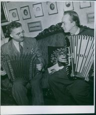 Carl Jularbo and another man sitting together and playing accordion.