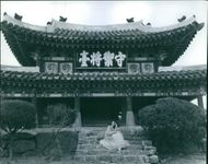 A photo of a woman posing and  siting on stairs of the historical hut wearing a Japanese costume. in Tokyo, Japan.