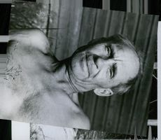 An old man facing the camera without his top on.