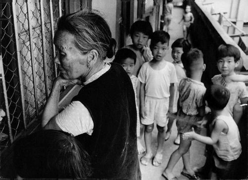 A photo of an old woman together with children standing in front of a window waiting for something.