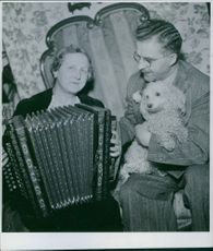 Carl Jularbo holding a dog while looking at this wife Alma play the accordion, 1943.