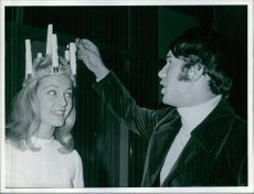 Man lightens candles in Kerstin Asp´s Lucia crown, 1968.