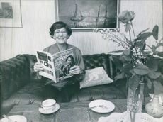 Woman siting, holding a magazine and facing camera.