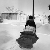 A woman carrying her belongings on a cart in the snow.