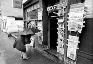 A man with umbrella reads the first pages on some newspapers outside a store