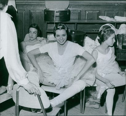 Women sitting on chairs.