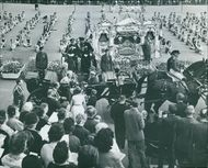 Queen Juliana being welcomed by the people on the street during an event.