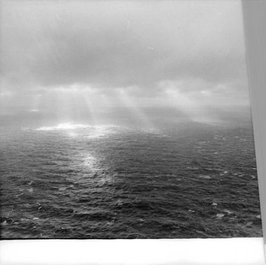 Sunrays coming out of clouds over sea.