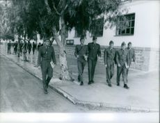 Juan Carlos de Borbón, King of Spain,  in uniform and walking on sidewalk with other soldiers. 1959.