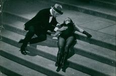 Robert Hossein with an unconscious woman lying on the stairs.