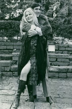 Pamela Tiffin is being hugged by a man.