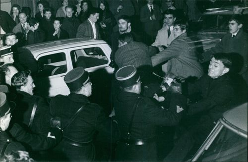 Cops stopping the men with people watching around, 1964.