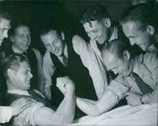 Two men doing hand wrestling and others looking at them. 1943
