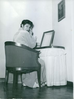A woman pictured looking over at the camera while grooming herself.
