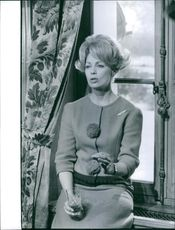 Dany Robin leaning by the window pane while having a glass of drink. 1963.