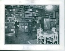 A photo of men standing in the library. 1930
