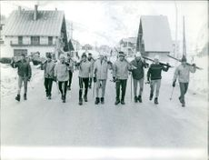 Skiers walking while carrying their skies equipment.