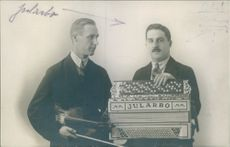 Carl Jularbo holding his accordion, a man looks at him.