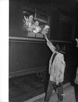 Children saying goodbye to a woman as they are leaving on a train.