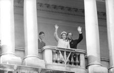 Prince Philip, Charles, Prince of Wales and Anne, Princess Royal waving from a balcony.