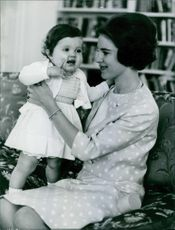 A photo of Princess Alexandra, The Honourable Lady Ogilvy with a baby. 1966