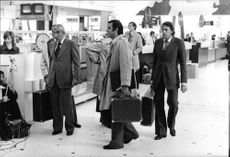 Jacques Brel standing with people holding suitcases