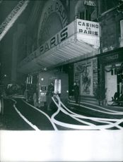 A vintage photo of a scene in Casino de Paris wherein firemen were fixing the water hose during a fire that happened in the building.