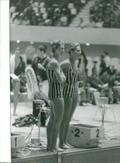 Women swimmers, standing, looking at the swimming pool, smiling.