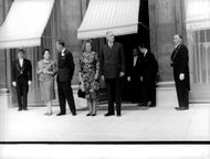 Charles de Gaulle and Queen Juliana with their spouses waiting for someone at the entrance.