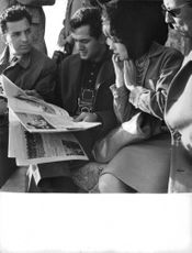 Pascale Petit  looking at a magazine with others, in Athens.