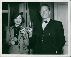 Maurice Chevalier with a woman, enjoying drink.