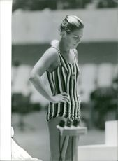 A woman swimmer standing, looking down.
