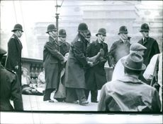 Policemen holding a wounded man and taking away.