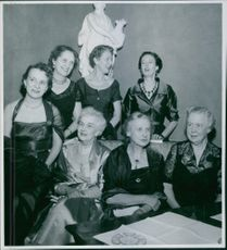 Women sitting together and photographed.