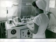 Nurse looking the baby in a machine, 1962.