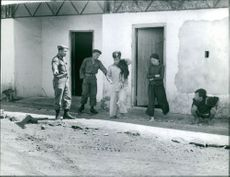 Indokina soldiers talking with civilians and telling them to move forward.  Taken - 16 Oct. 1961