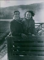 Two Italian civilian women riding on a wagon and smiling, 1944.