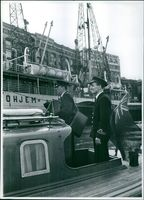 Two men in uniform standing on a boat, 1957.