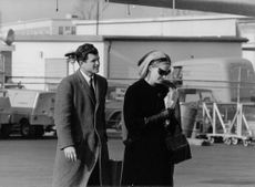 """Edward Moore """"Ted"""" Kennedy walking with a man."""
