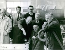 A man pointing at something while talking to another man, other people standing there looking at them and smiling.