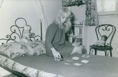 A LADY PLAYING CARD IN HER BED