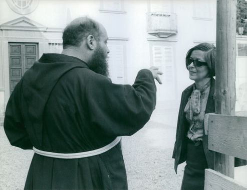 A priest talking to a girl.
