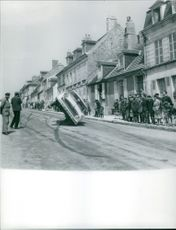 A car turned downwards on the street driven by Jean Sunny.