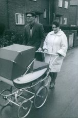 Joseph Dykes walking with he wife and baby in street and smiling.