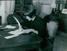 Bettina is writing using a quill pen.