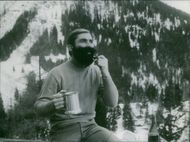 Karl Schranz holding a mug while smoking a pipe in the Alps.