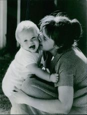 A woman kissing her child.