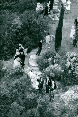 Princess Maria Gabriella walking on lawn with other companions.