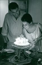 Robert Hossein looking at the woman blowing candles.